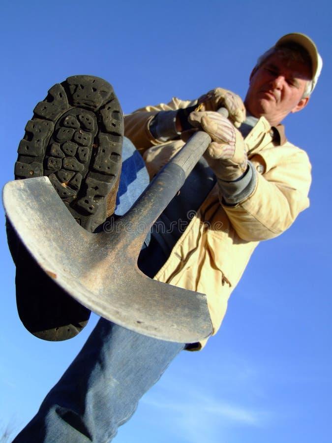 Fazendeiro sênior que escava com pá imagem de stock