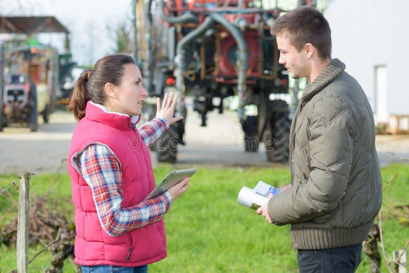 Fazendeiros que discutem a gestão da colheita no trator dianteiro imagem de stock royalty free