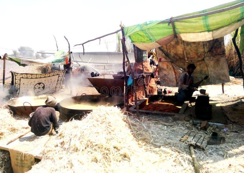 Fazendeiros que fazem o açúcar mascavado (jaggery) em india rural imagens de stock