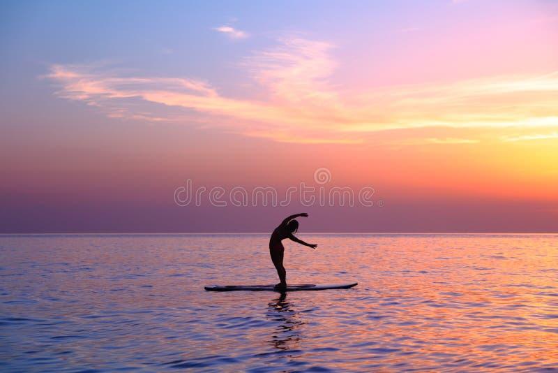 Fazendo asanas da ioga na praia imagem de stock