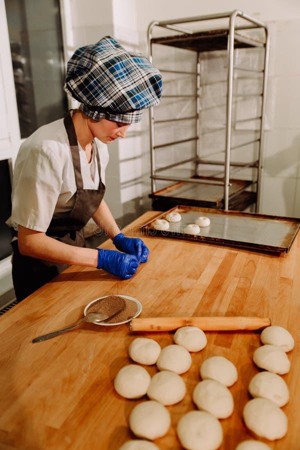 Fazendo bolos de canela Massa de fermento crua caseiro após o levantamento pronto para cozer imagem de stock