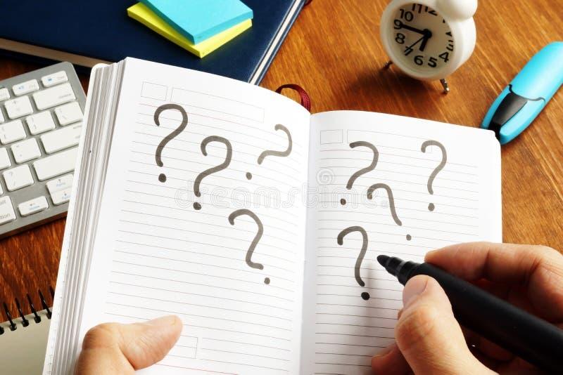 Fazendo a decisão e incerto Pontos de interrogação na nota foto de stock royalty free