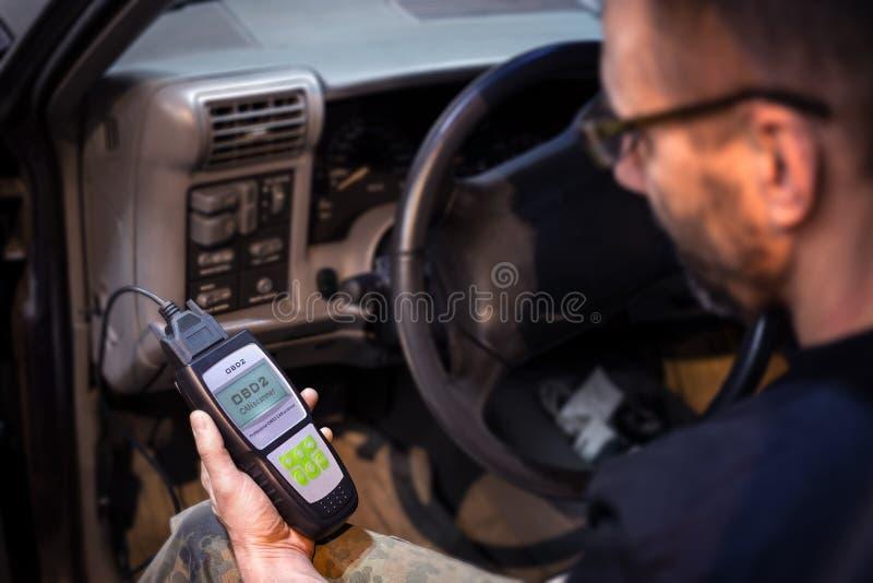 Fazendo diagnósticos do carro usando o dispositivo do obd foto de stock