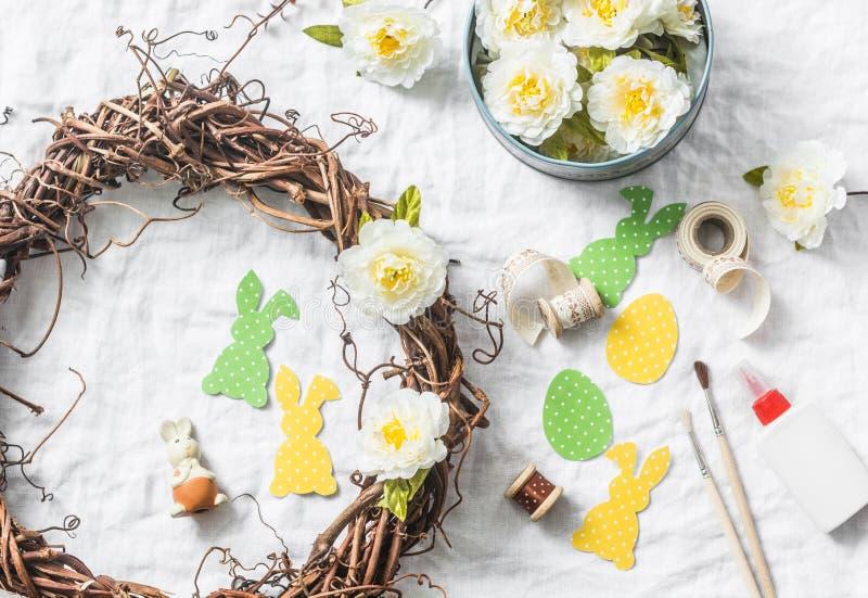 Fazendo a grinalda caseiro da Páscoa das videiras com flores, forre os coelhos, fitas em um fundo branco, vista superior Decorati foto de stock royalty free