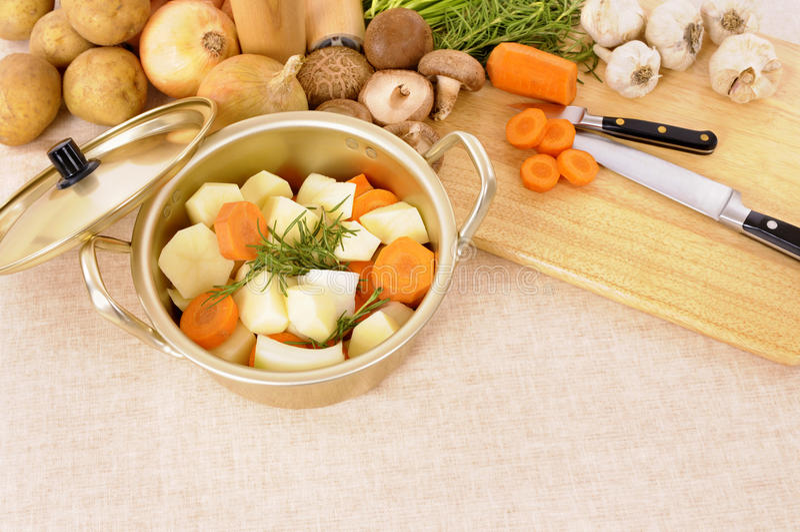 Fazendo inverno a caçarola tornar côncava ou a panela com vegetais e placa de desbastamento orgânicos imagens de stock royalty free