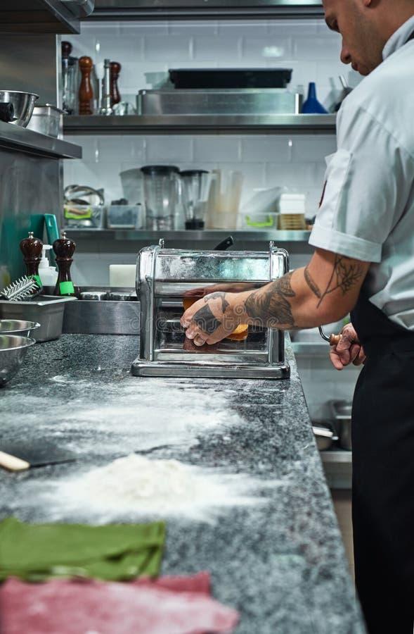 Fazendo a massa Imagem vertical das mãos do cozinheiro chefe com as tatuagens que rolam uma massa através da máquina da massa na  fotografia de stock royalty free