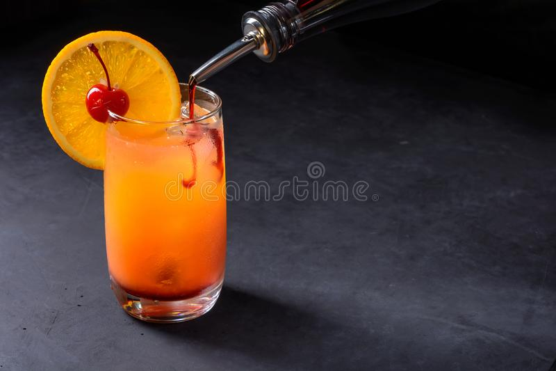 Fazendo o cocktail do nascer do sol do tequila O xarope de groselha derramou lentamente em um vidro do gelo, do suco de laranja e fotos de stock