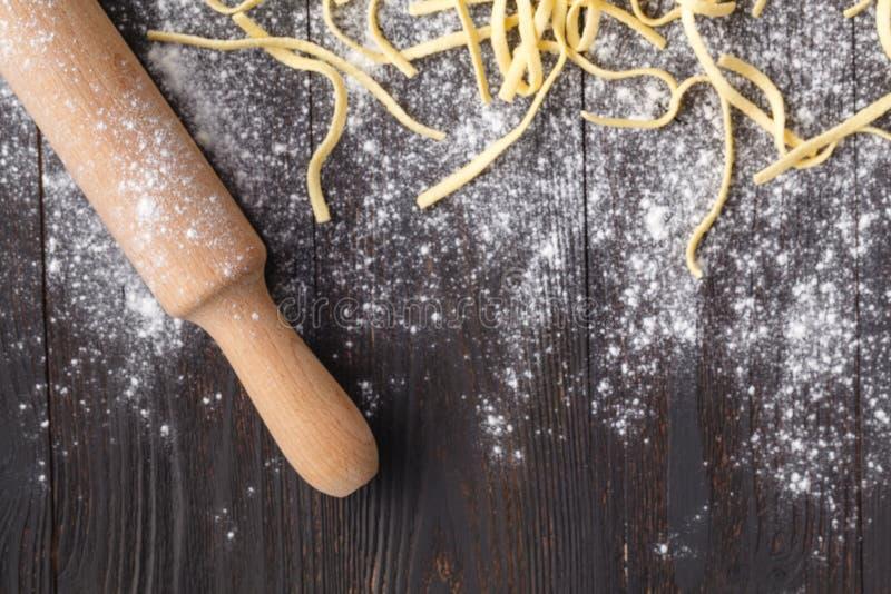 Fazendo o linguine caseiro da massa na mesa de cozinha rústica com flou imagem de stock