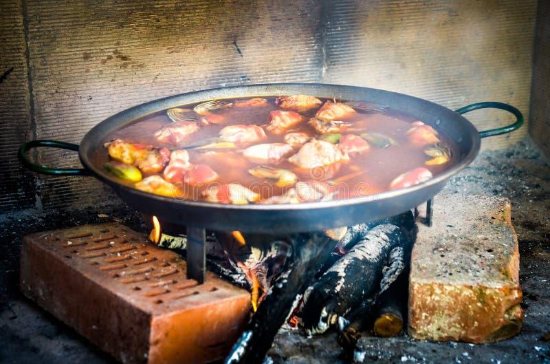 Fazendo o paella espanhol tradicional sobre o fogo aberto com carvão de madeira fotografia de stock