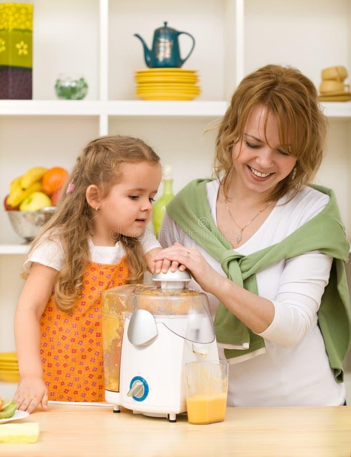 Fazendo o suco de fruta com mamã fotografia de stock royalty free
