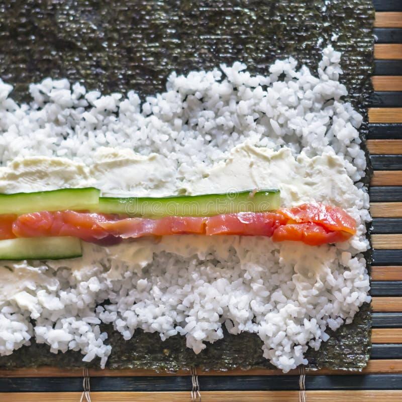 Fazendo o sushi Rolls: Salmon Fish Strips, varas do pepino, queijo creme, arroz e Nori Seaweed Sheet em uma esteira de bambu foto de stock royalty free