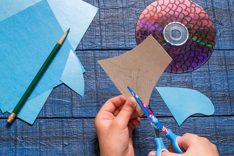 Fazendo peixes do brinquedo do CD Children& feito a mão x27; projeto de s Etapa 3 foto de stock royalty free
