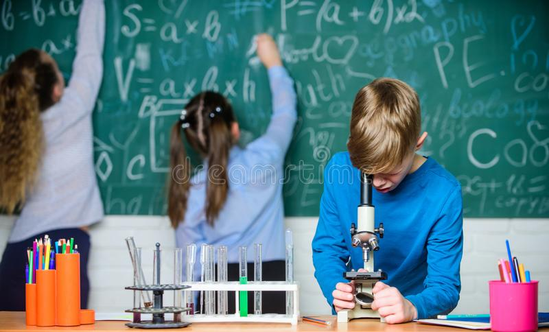 Fazendo a pesquisa Crian?as que aprendem a qu?mica no laborat?rio da escola Pouco crian?as no laborat?rio Microsc?pio da qu?mica fotos de stock
