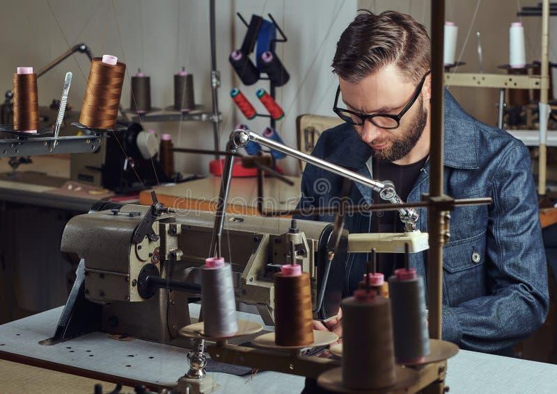 Fazendo a roupa costure o assento na tabela e o trabalho em uma máquina de costura na oficina da costura fotos de stock