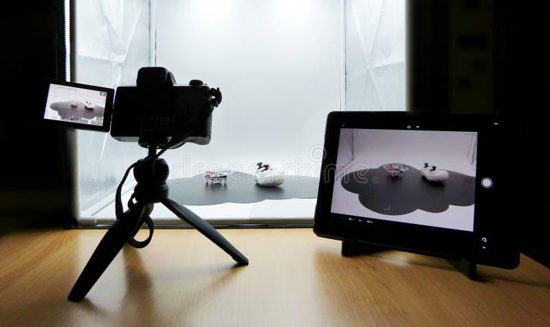 Fazendo um tiro do estúdio usando uma caixa leve Câmera no tripé, grupo da tabuleta no controlo a distância da câmera fotografia de stock royalty free