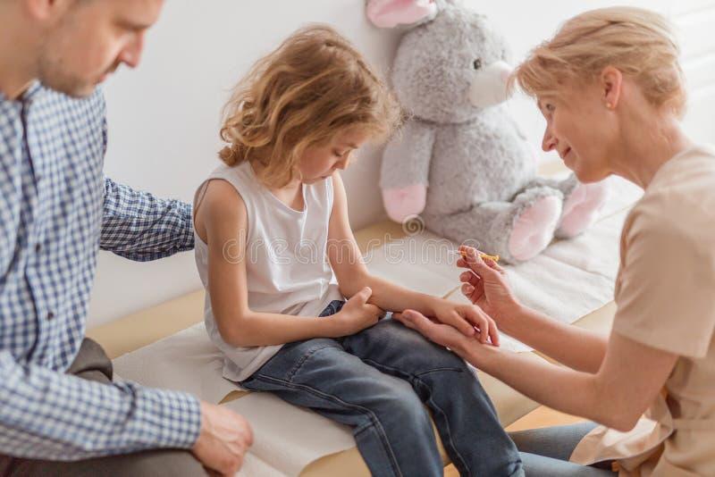 Fazendo uma injeção a um menino pequeno durante uma visita à clínica médica foto de stock royalty free