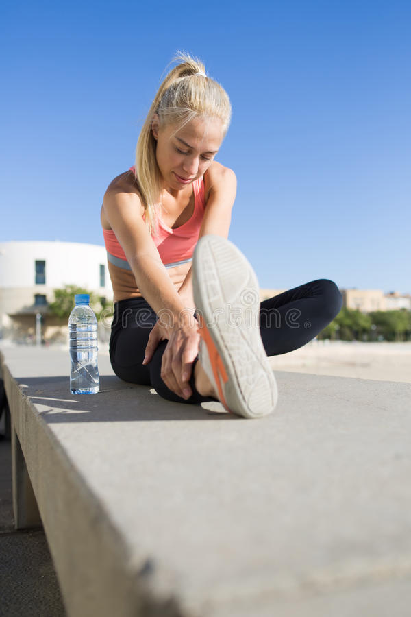Fazer apto da mulher dos jovens aquece exercícios antes que comece manhã corrida no ar fresco fotos de stock