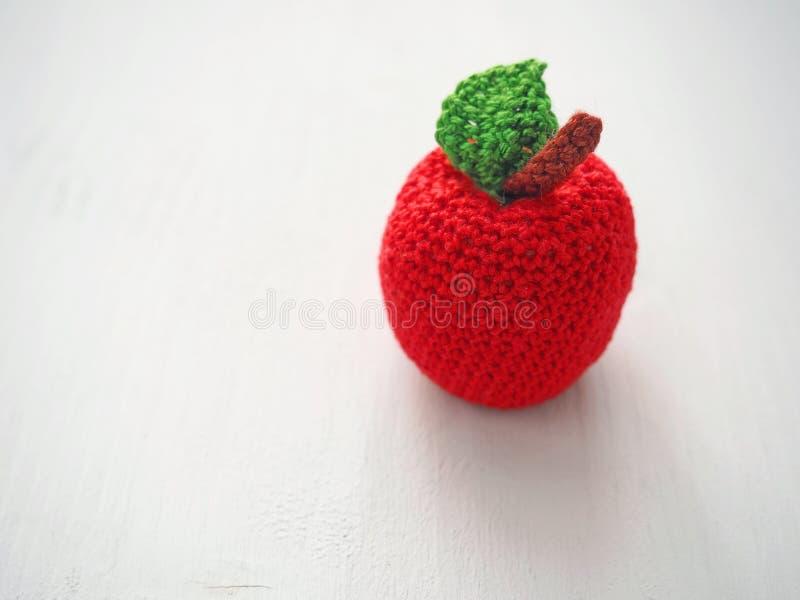 Fazer crochê ascendente próximo da maçã Brinquedos feitos malha Foco seletivo fotografia de stock