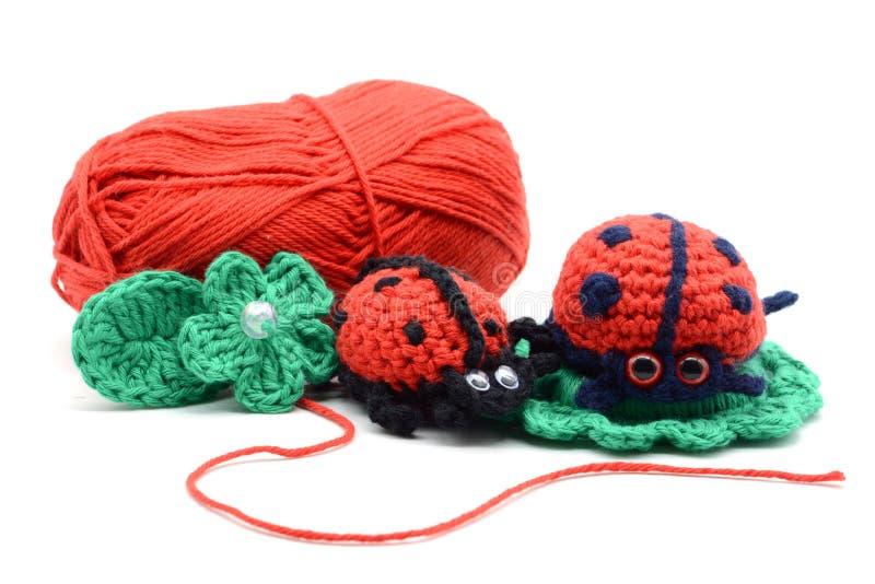 Fazer crochê o joaninha no fundo isolado branco Bola vermelha de lãs imagem de stock royalty free