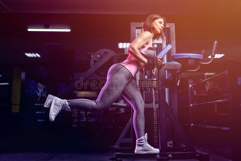 Fazer da mulher da aptidão investe contra exercícios para o treinamento do exercício do músculo do pé no gym fotografia de stock