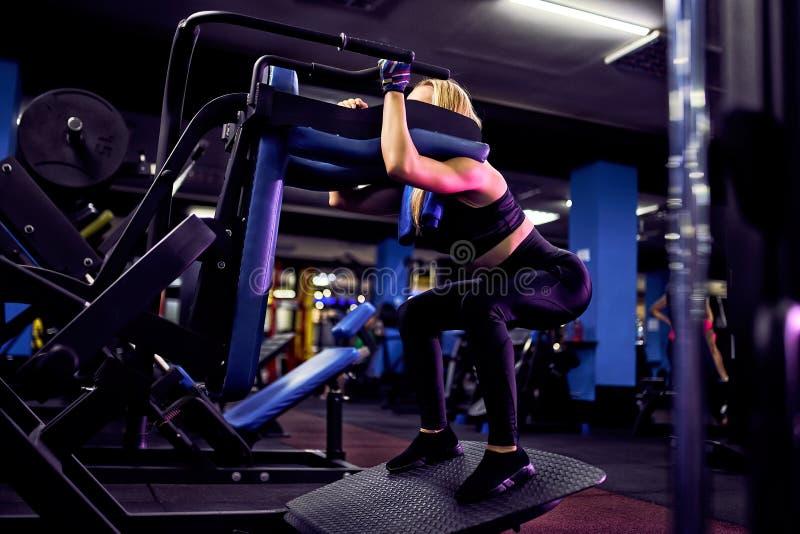 Fazer da mulher da aptidão investe contra exercícios para o treinamento do exercício do músculo do pé no gym foto de stock
