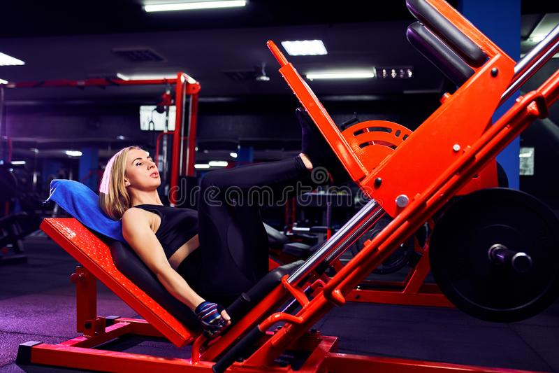 Fazer da mulher da aptidão investe contra exercícios para o treinamento do exercício do músculo do pé no gym imagem de stock royalty free
