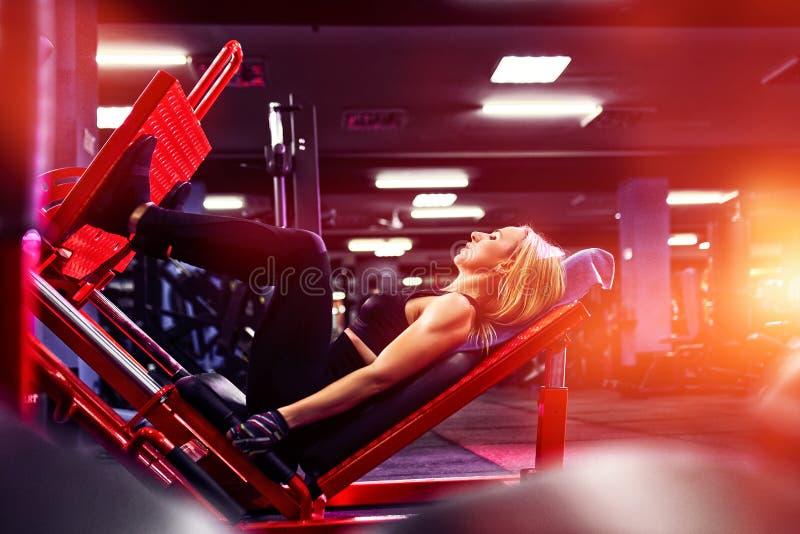 Fazer da mulher da aptidão investe contra exercícios para o treinamento do exercício do músculo do pé no gym imagem de stock
