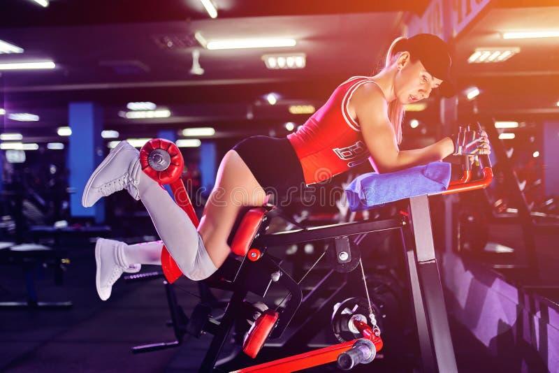 Fazer da mulher da aptidão investe contra exercícios para o treinamento do exercício do músculo do pé no gym foto de stock royalty free