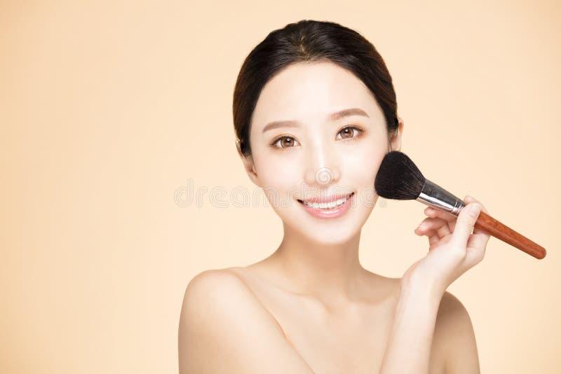 Fazer da mulher compõe na cara com a escova cosmética fotos de stock