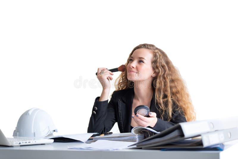 Fazer da mulher de negócio compõe em seu escritório durante o trabalho fotografia de stock royalty free