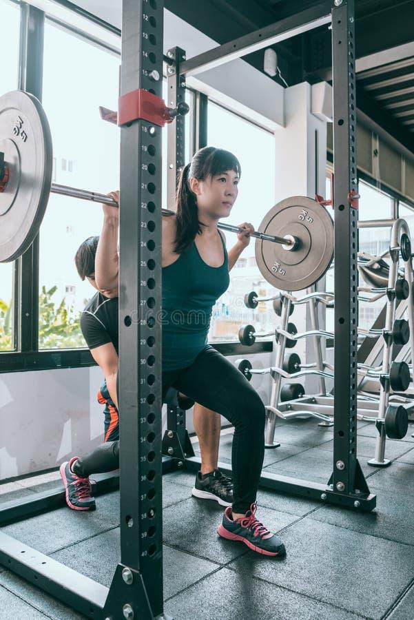 Fazer da mulher investe contra com o barbell no gym imagens de stock