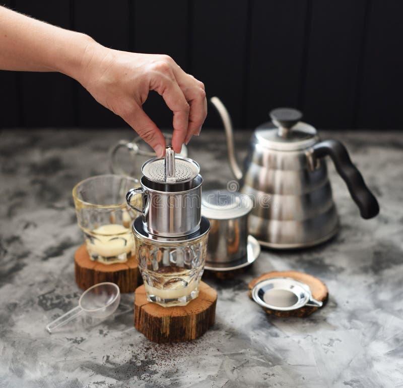 Fazer derrama sobre o café vietnamiano do leite Café da pressão de mão da mulher no phin no fundo escuro foto de stock royalty free