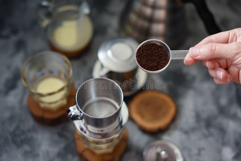 Fazer derrama sobre o café vietnamiano do leite Café de derramamento da mão da mulher no phin no fundo escuro foto de stock royalty free