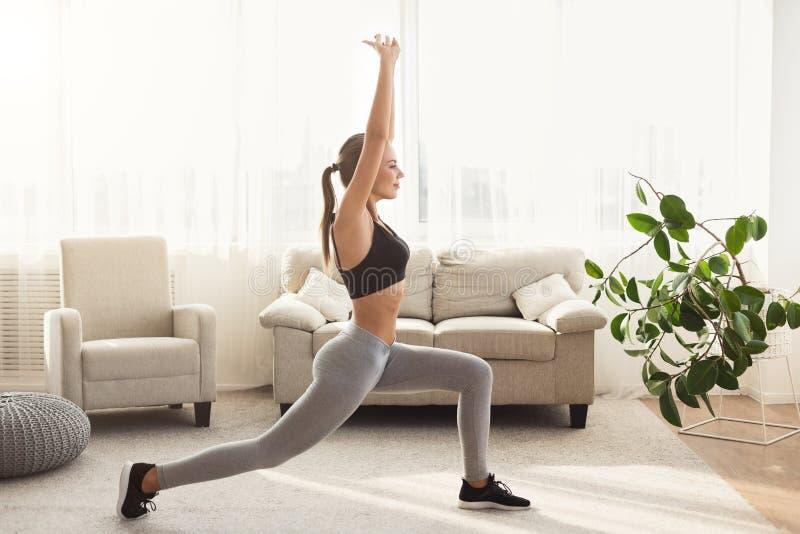 Fazer desportivo da menina investe contra o exercício em casa imagens de stock