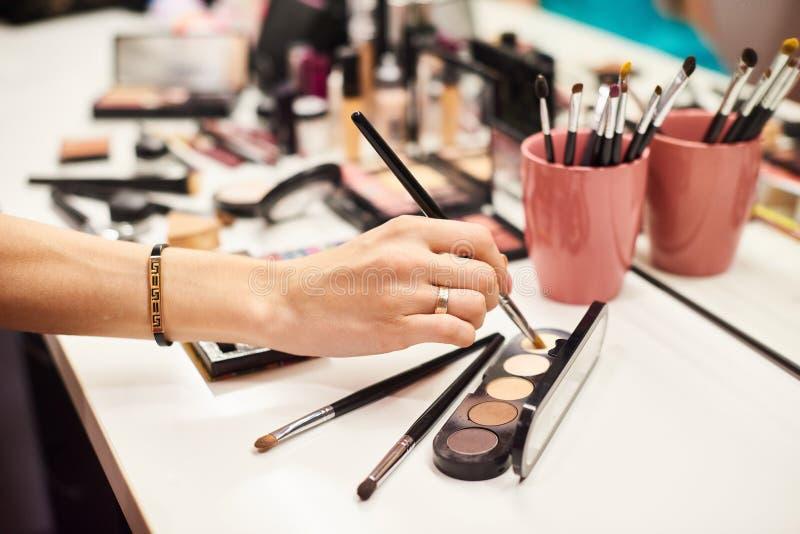 Fazer do maquilhador perfeito para compensar pelo modelo novo no estúdio da foto fotos de stock royalty free