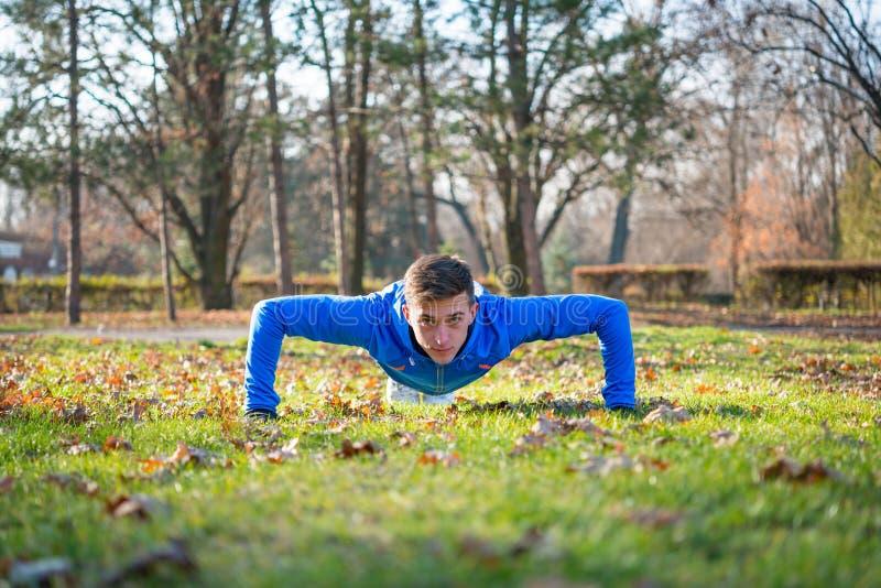 Fazer masculino do corredor levanta no gramado verde no parque em Sunny Autumn Morning Estilo de vida e conceito saudáveis do esp fotos de stock