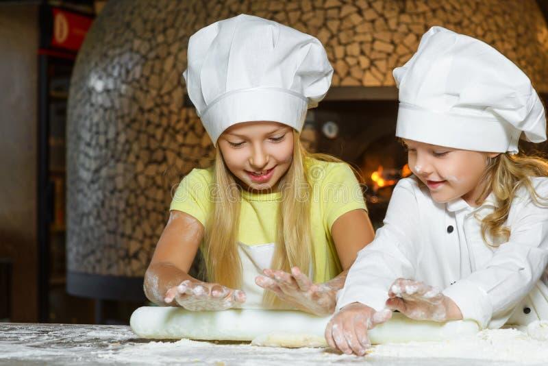 Fazer a massa para a pizza é divertimento - cozinheiros chefe pequenos imagem de stock