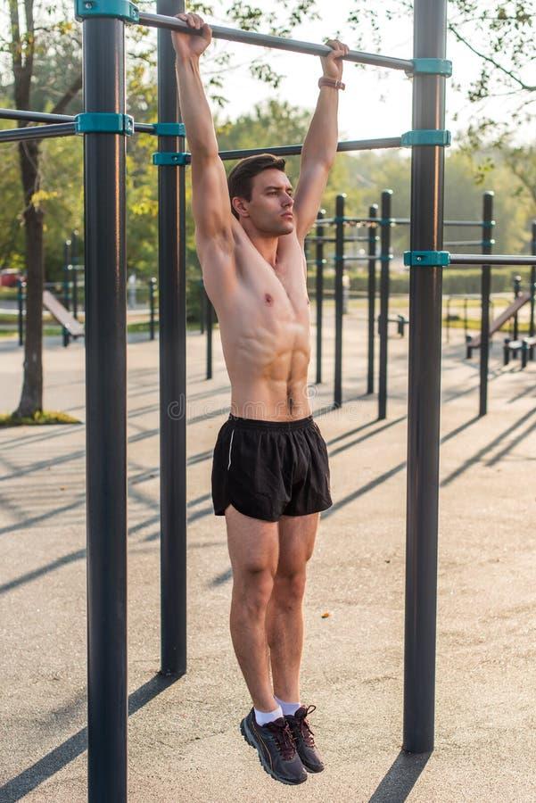Fazer muscular novo do atleta levanta os exercícios que penduram com braços retos em uma barra horizontal no parque imagem de stock royalty free