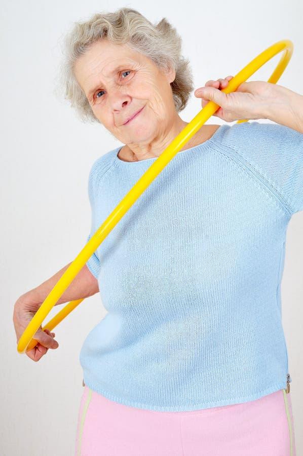 Fazer sênior da mulher ginástico com hula-aro imagens de stock