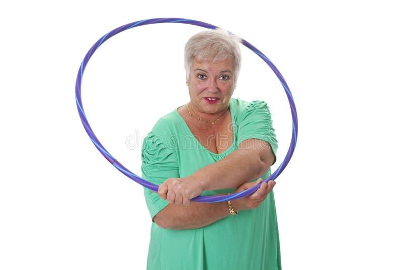 Fazer sênior da senhora ginástico com hula-aro fotografia de stock royalty free