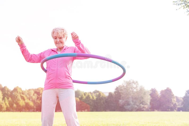 Fazer superior ativo da mulher ginástico com a aro do hula no parque imagem de stock