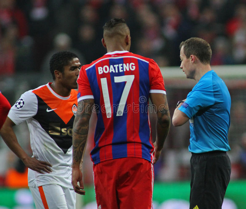 FC Bayern Muenchen v FC Shakhtar Donetsk - UEFA Champions League. MUNICH, GERMANY - MARCH 11 2015: Referee William Collum gives Shaktar's midfielder Douglas royalty free stock images