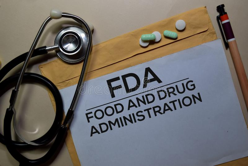 FDA - Texto de la Administración de Alimentos y Medicamentos sobre el sobre marrón y el estetoscopio Salud o concepto médico fotos de archivo