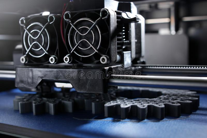 FDM 3D打印机制造业从银灰色细丝的正齿轮在明亮的光的方案磁带上 免版税库存照片