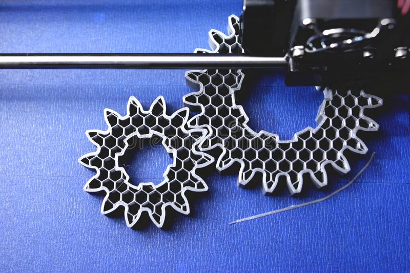 FDM 3D-printer manufacturing spur gears from silver-gray filament on blue print tape - top view royalty free stock photography