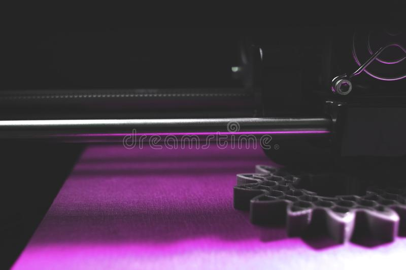 FDM 3D-printer manufacturing spur gears from silver-gray filament on magenta print tape - dimmed part view stock photos