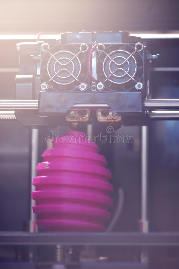 FDM 3D-printer manufacturing wound pink easter egg sculpture - front view on object and print head stock image