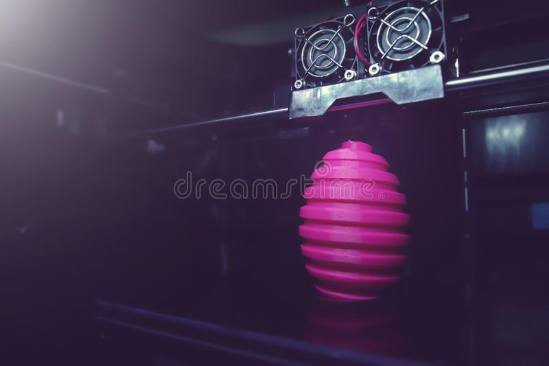 FDM 3D-printer manufacturing wound pink easter egg sculpture - wide angle view on object, print head and machine chamber stock image