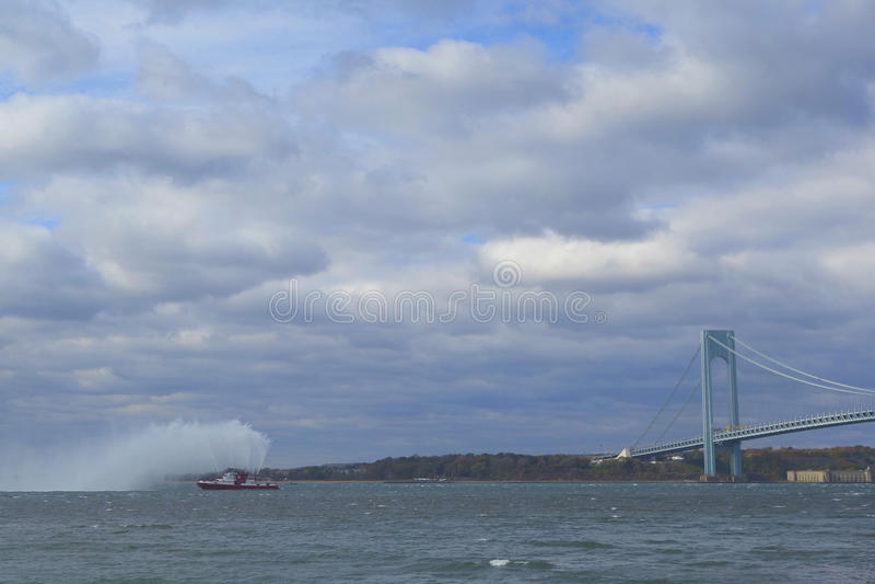FDNY Fireboat rozpyla wodę w powietrze świętować początek Miasto Nowy Jork maraton 2014 w przodzie Verrazano most obraz stock