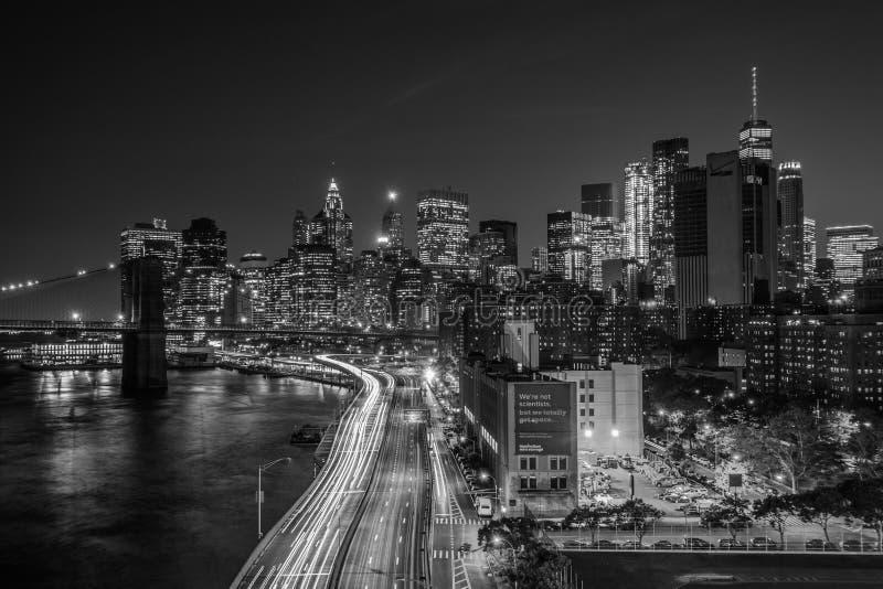 FDR驱动看法和曼哈顿下城地平线在晚上,从曼哈顿大桥走道,纽约 免版税库存图片